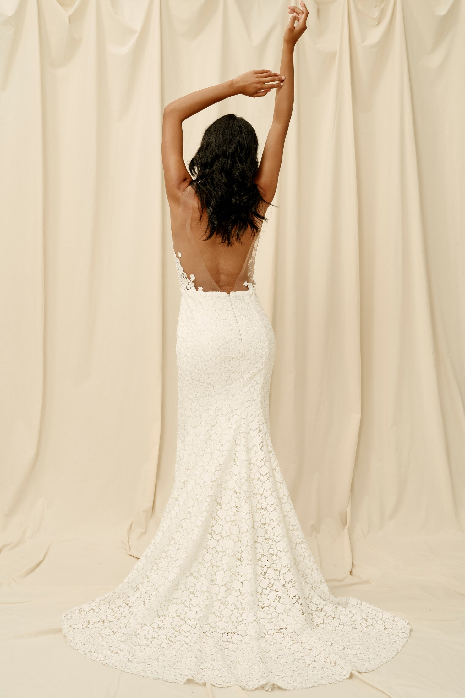 Backless lace wedding dress with a fitted skirt and long train
