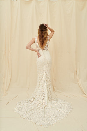 Mermaid wedding dress with all-over tiny flower lace, a dramatic train, and a low back