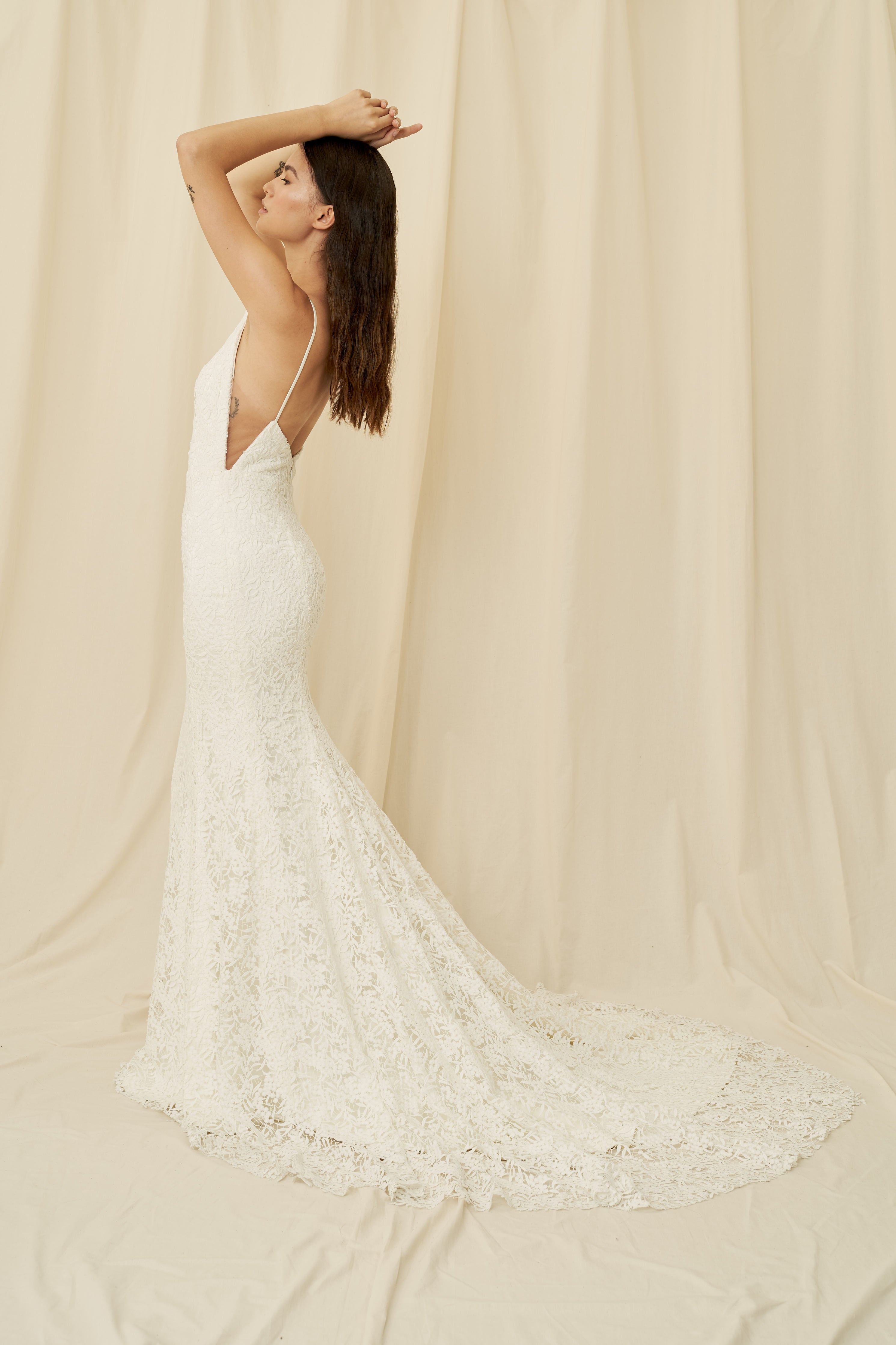 A high-neck wedding dress with all-over botanical lace and a long train