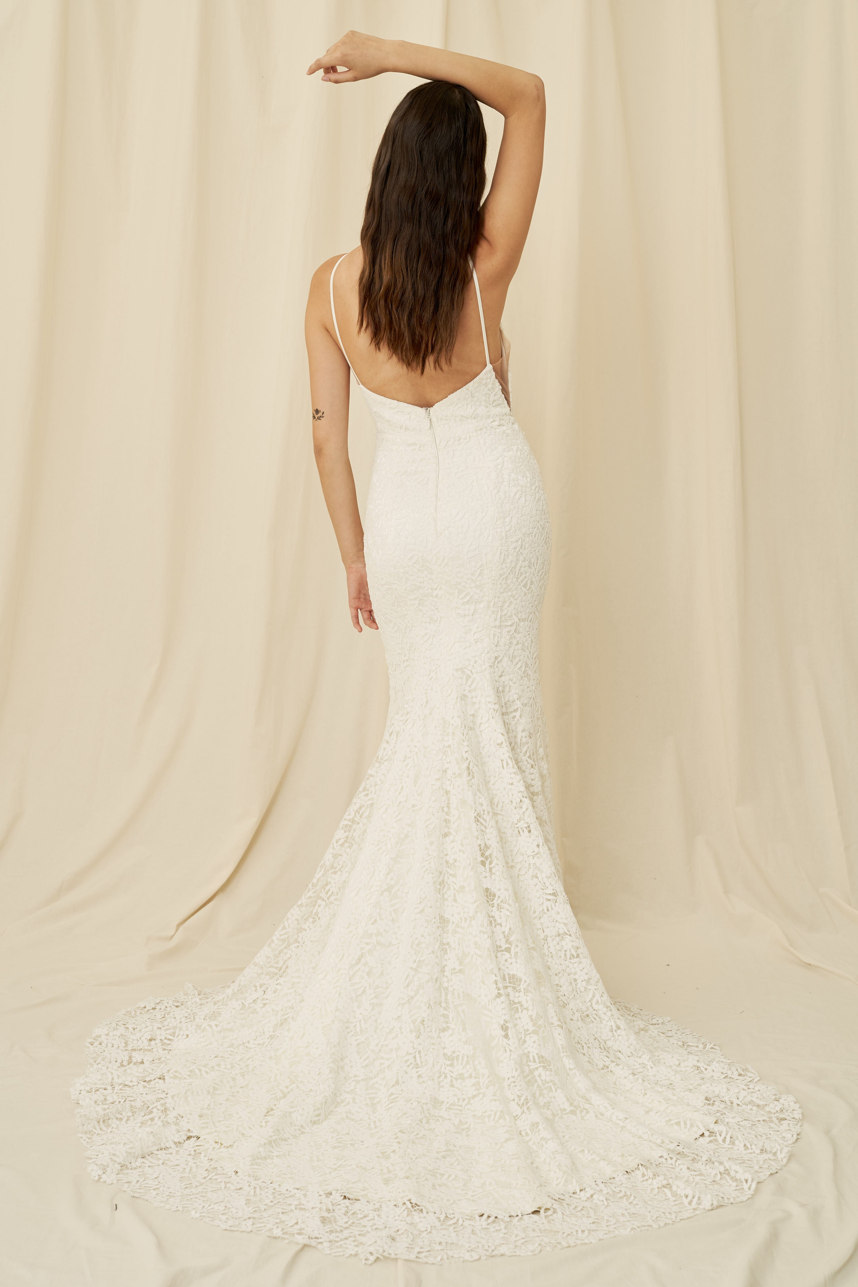 A high-neck lace wedding dress with a low back and a long train