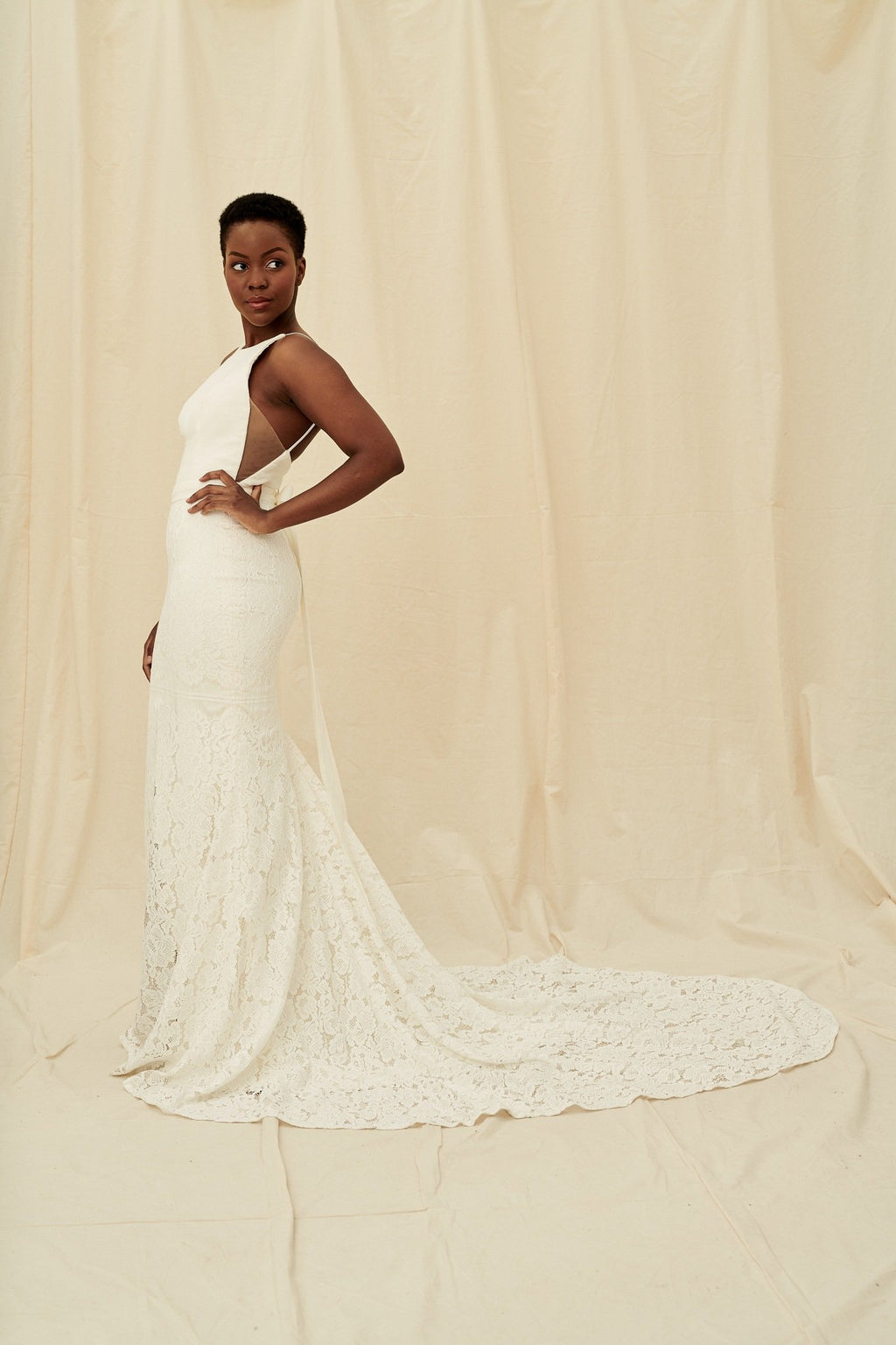 A fitted, high-neck crepe lace gown with a hidden leg slit and a built-in bow