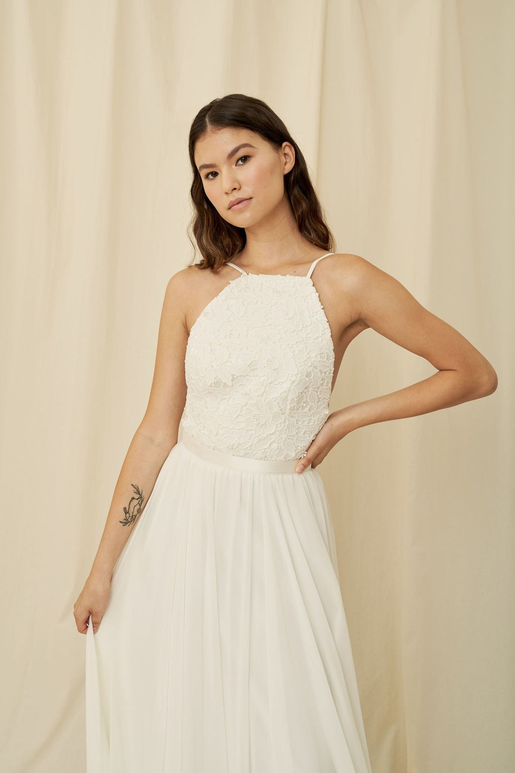 Clean cut high-neck wedding dress with floral lace, wrap ties, and a flowy chiffon skirt