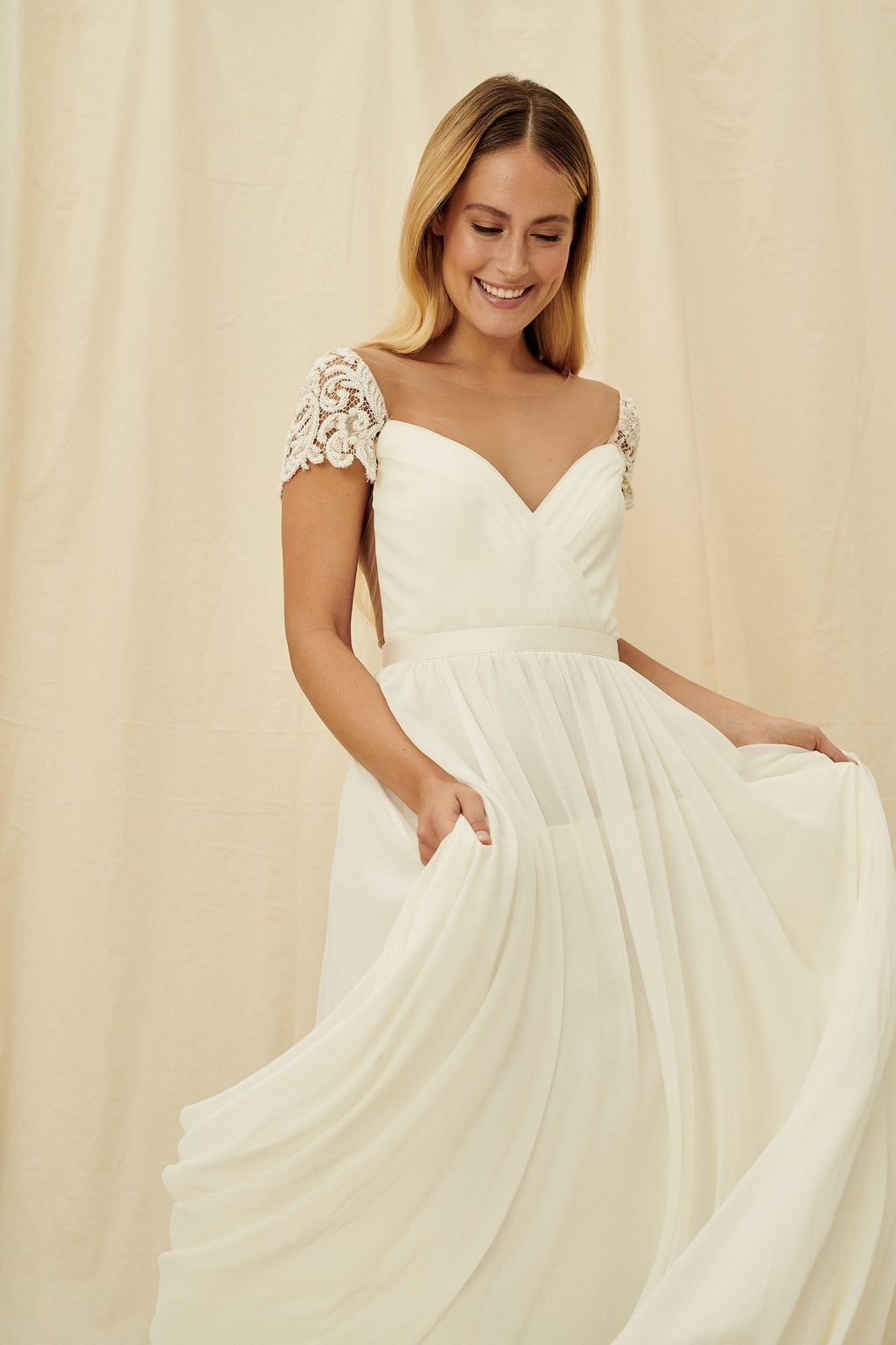 A romantic wedding dress with an illusion back and beaded lace cap sleeves by Truvelle
