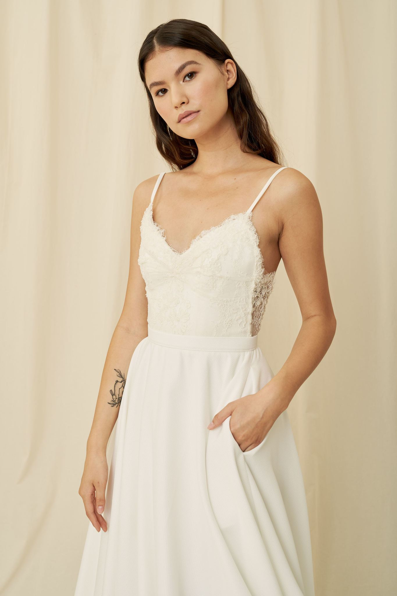 A romantic wedding dress with a backless lace bodice, button up back, and crepe skirt with pockets by Truvelle