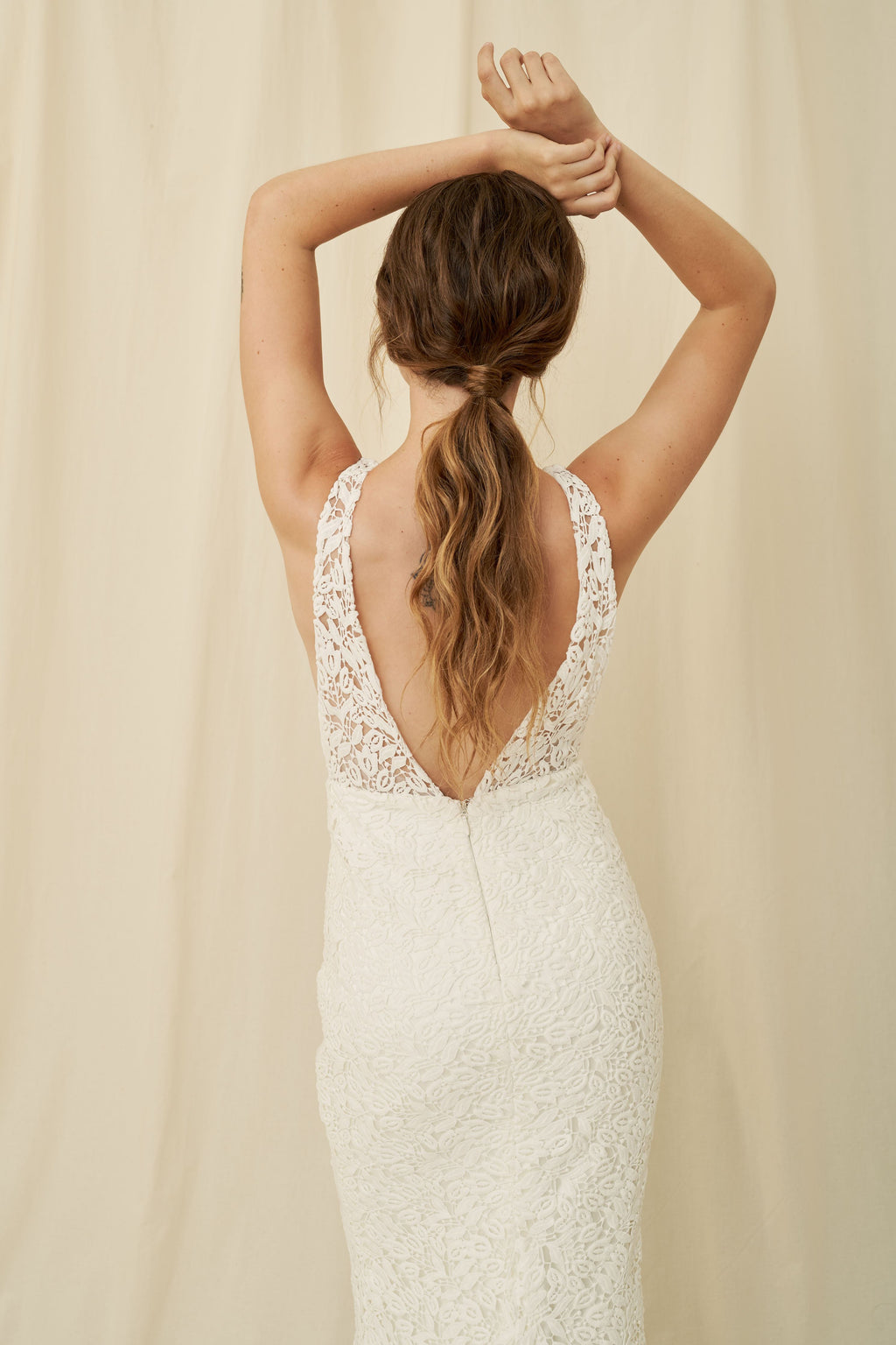 A low-cut mermaid wedding gown with unique lace and a long train