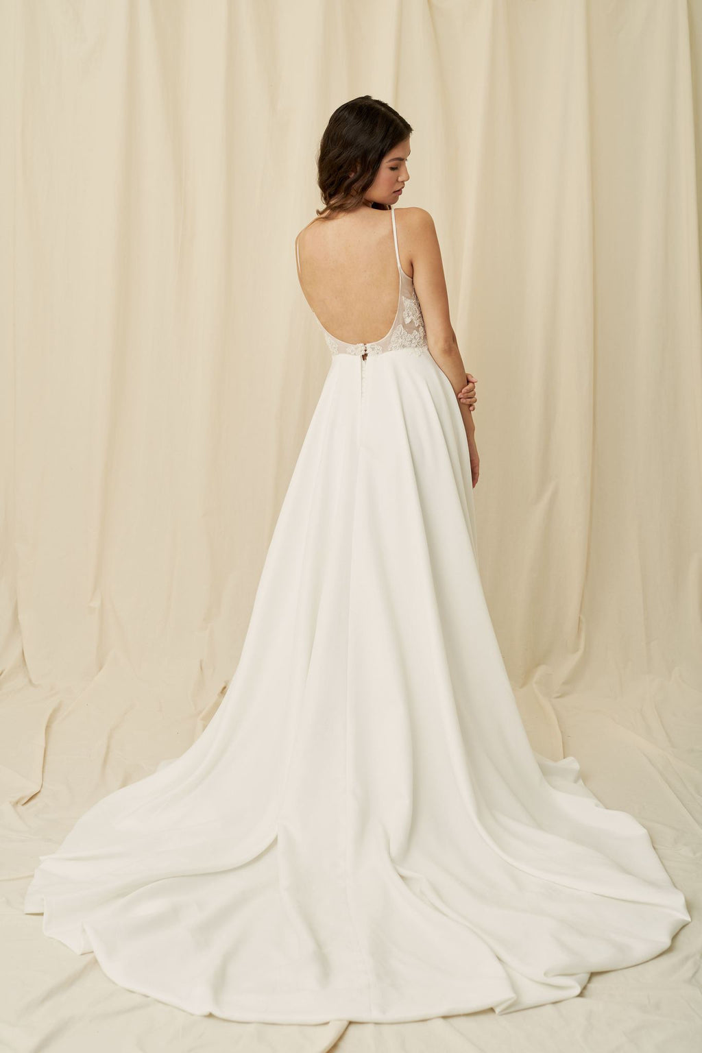 Crepe wedding dress with lace sides, a low back, and pockets