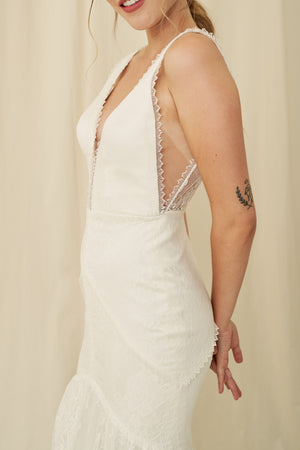 A unique boho-chic fitted wedding dress with lace trim detailing