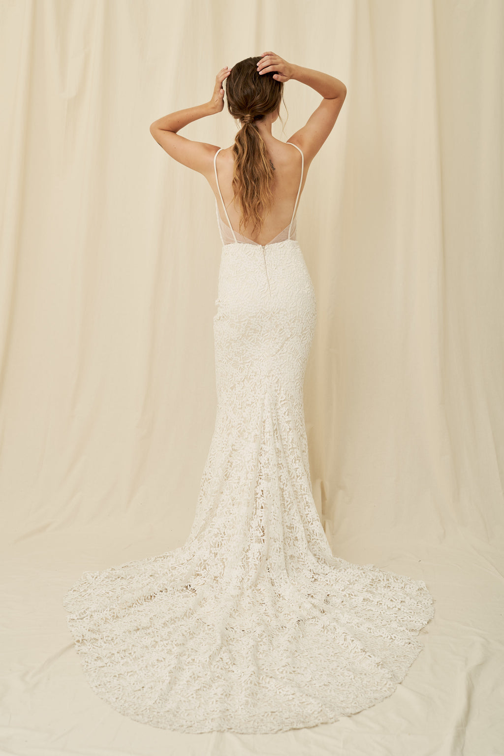 A botanical lace mermaid wedding gown with a plunging neckline and long train