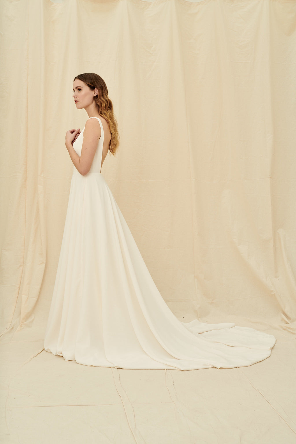Backless crepe wedding dress with a long train and pockets
