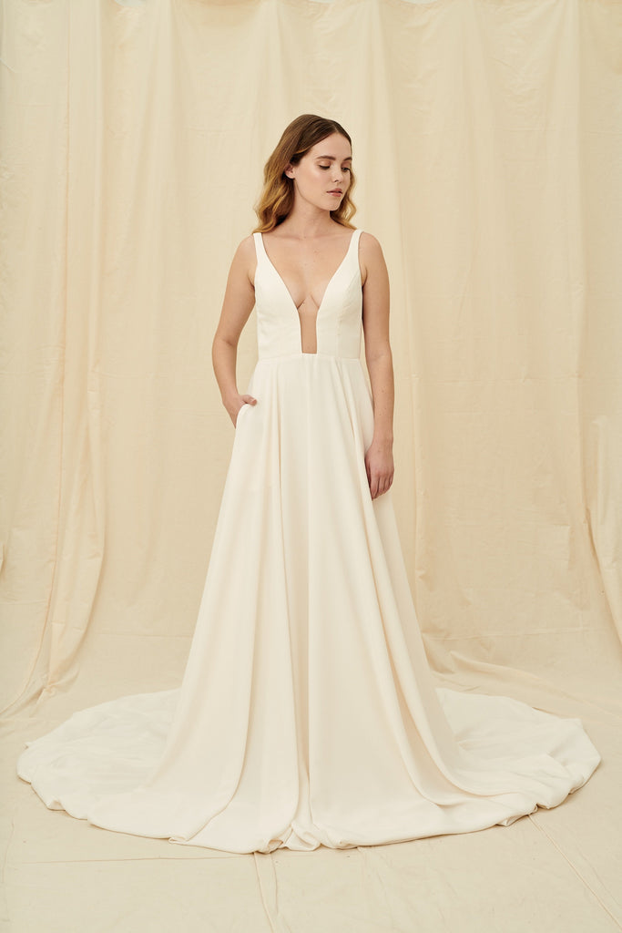 Minimalist crepe wedding dress with a long train and pockets