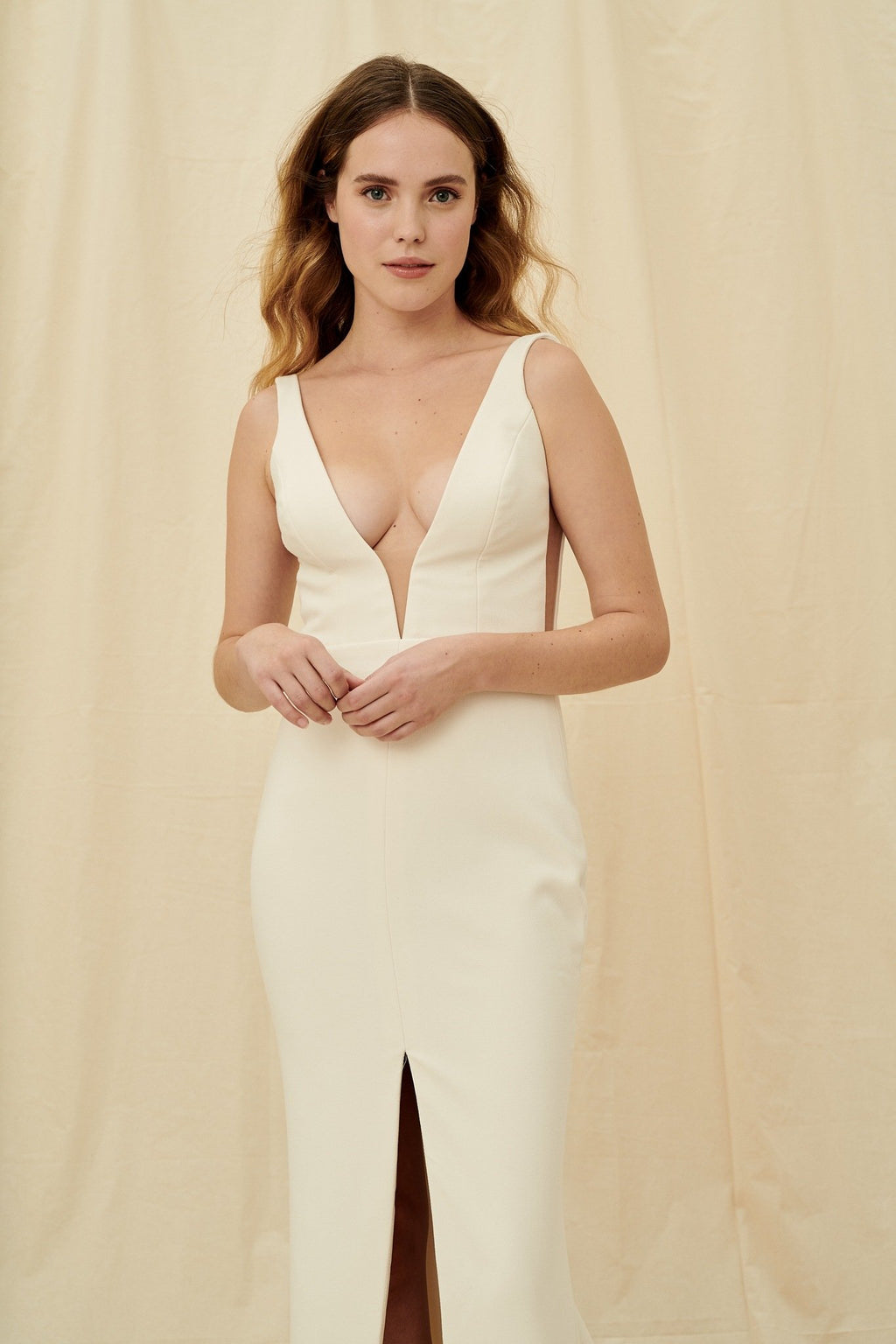 Simple low cut crepe wedding gown with a deep v back and a centre slit skirt