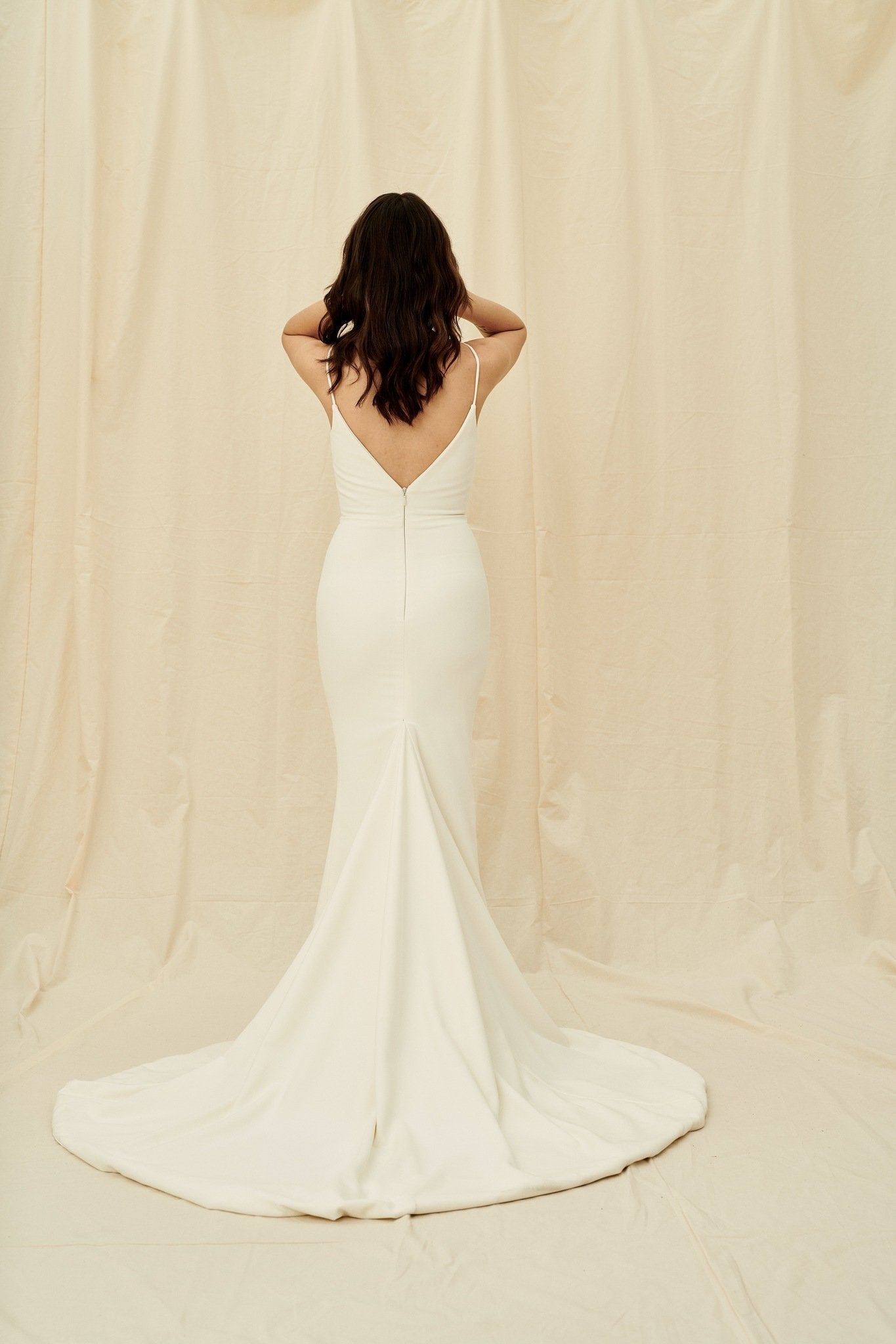 Low back crepe wedding dress with a fitted mermaid skirt and a train