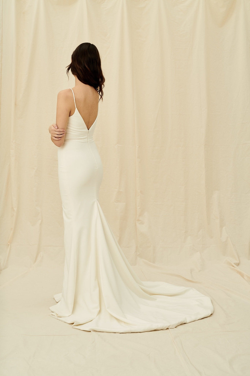 Simple fitted crepe wedding dress with spaghetti straps and a slit skirt