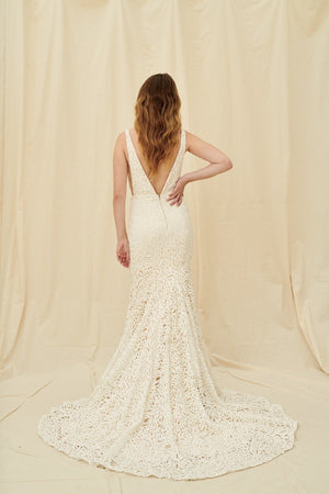 Deep v mermaid wedding gown with bold modern lace, a low back, and a sweeping train
