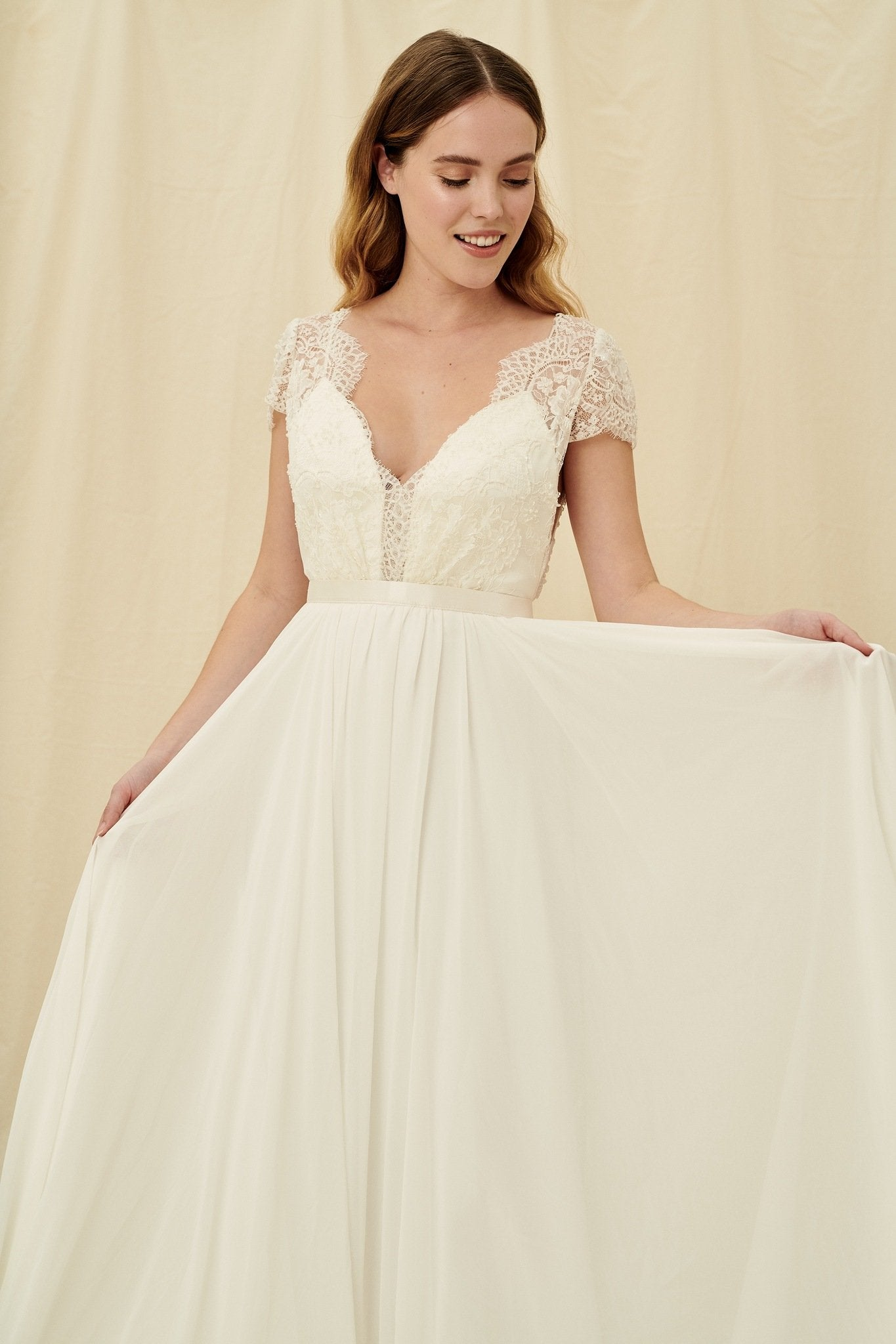 Low back wedding gown with beaded lace cap sleeves and a flowy chiffon skirt