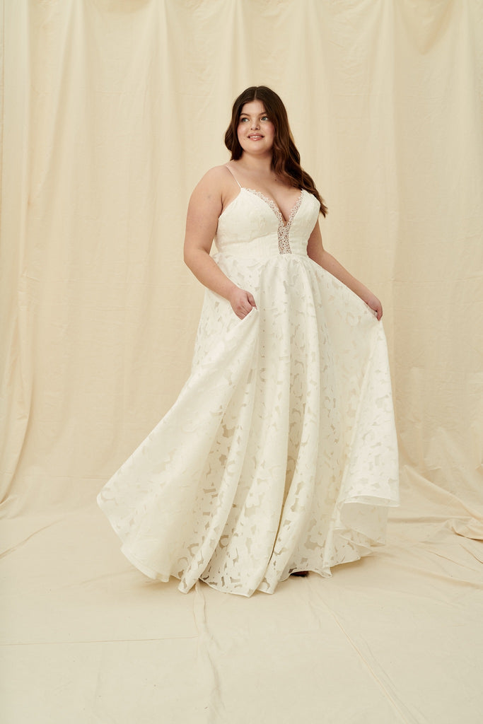 Plus size wedding dress with a low neckline, corset back, and a textured floral lace