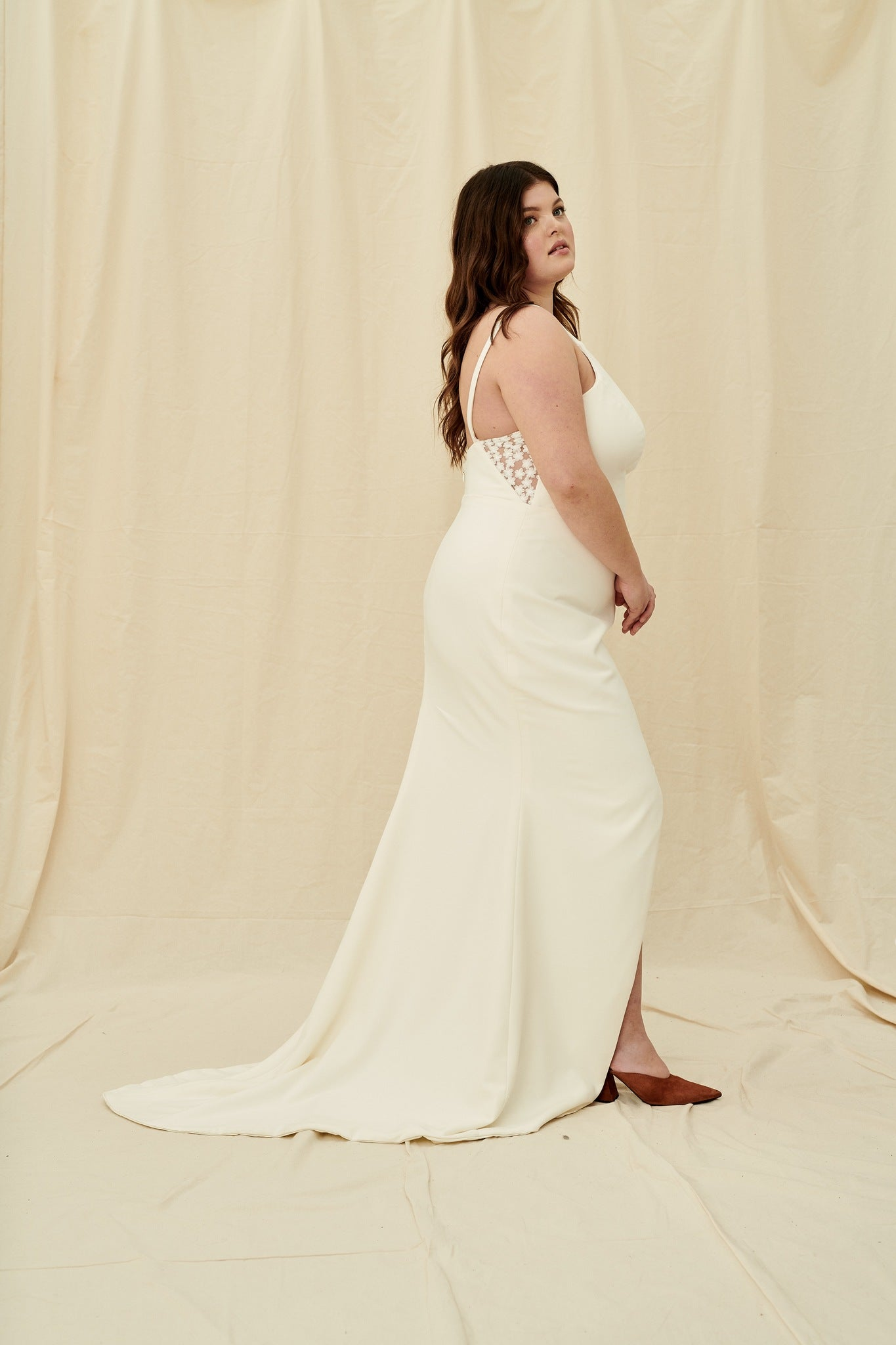 Curvy crepe wedding dress with a high neck, low back, sheer lace panels, and a slit skirt