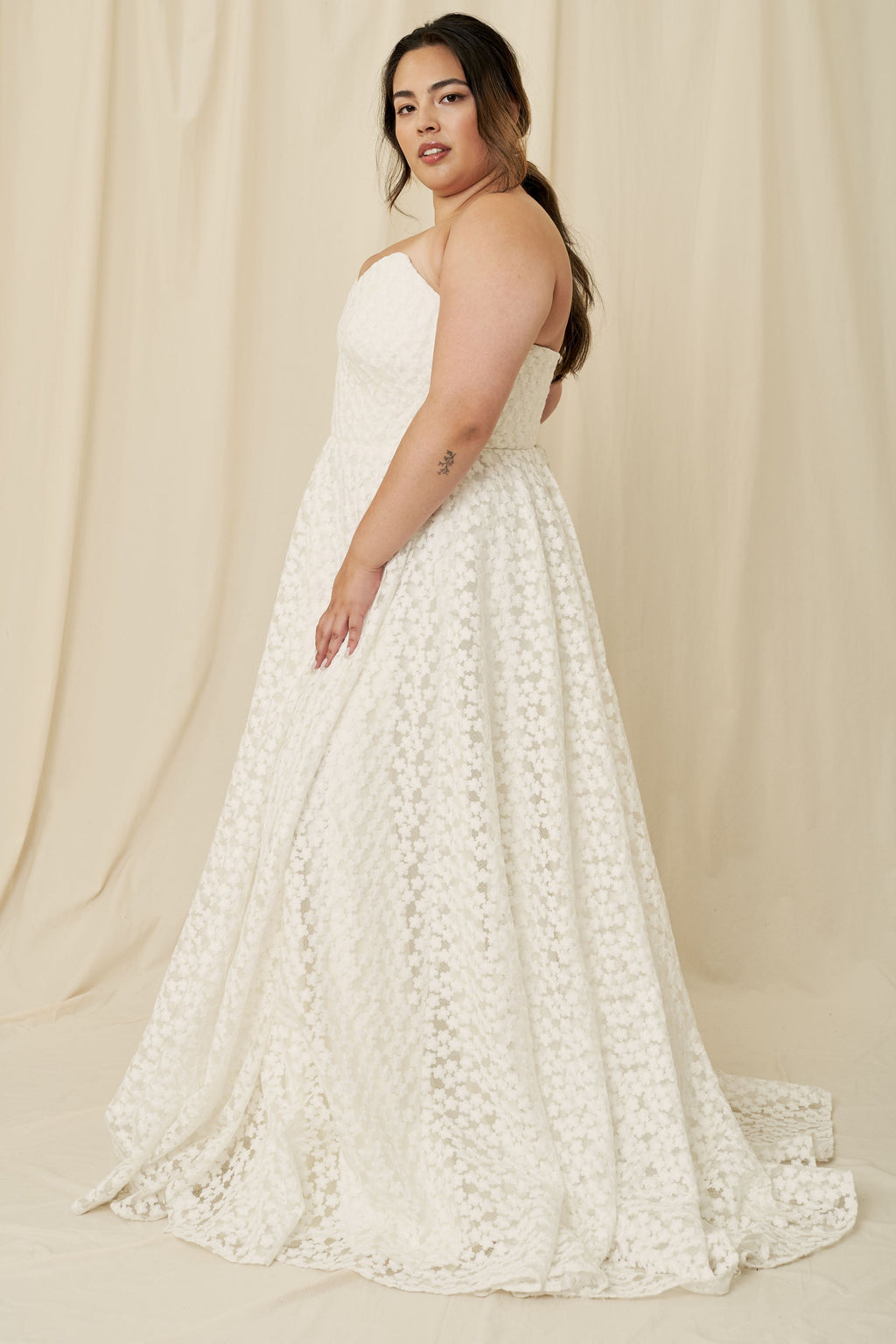 A plus size wedding dress with a strapless silhouette, corset back tie, and all-over floral daisy lace