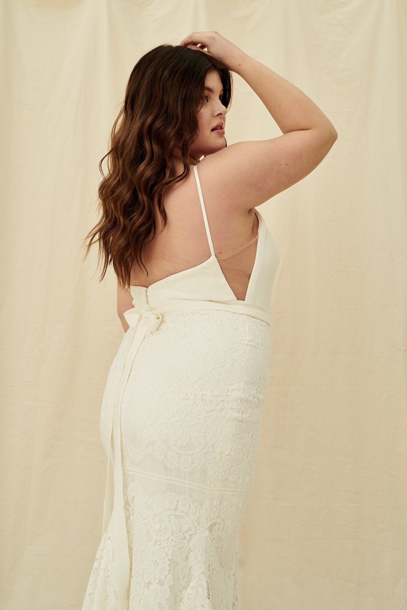 A high-neck plus size wedding gown with a skirt slit and belt