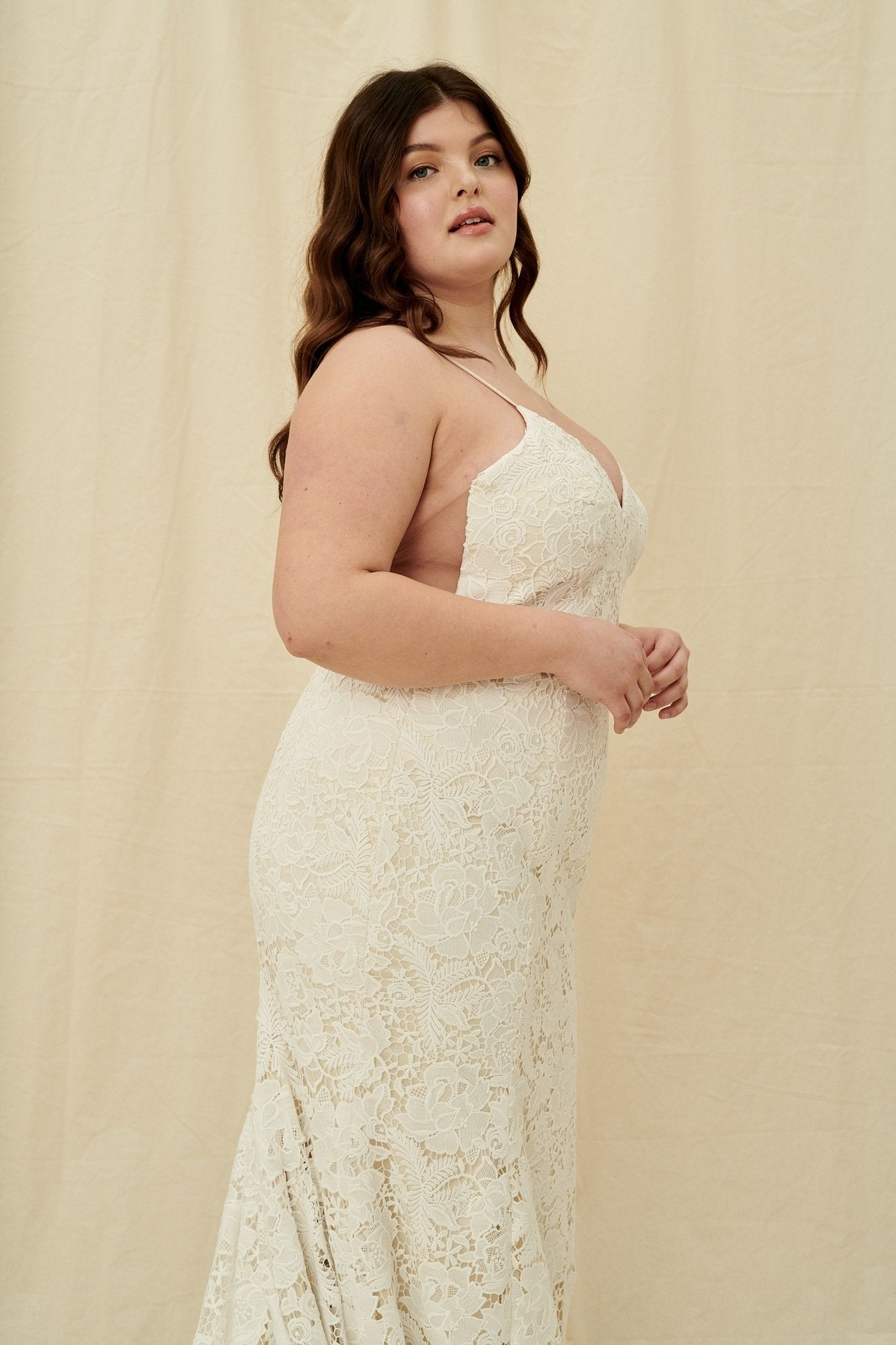 Fitted lace wedding gown for curvy sizes, with spaghetti straps, an open back, and a train