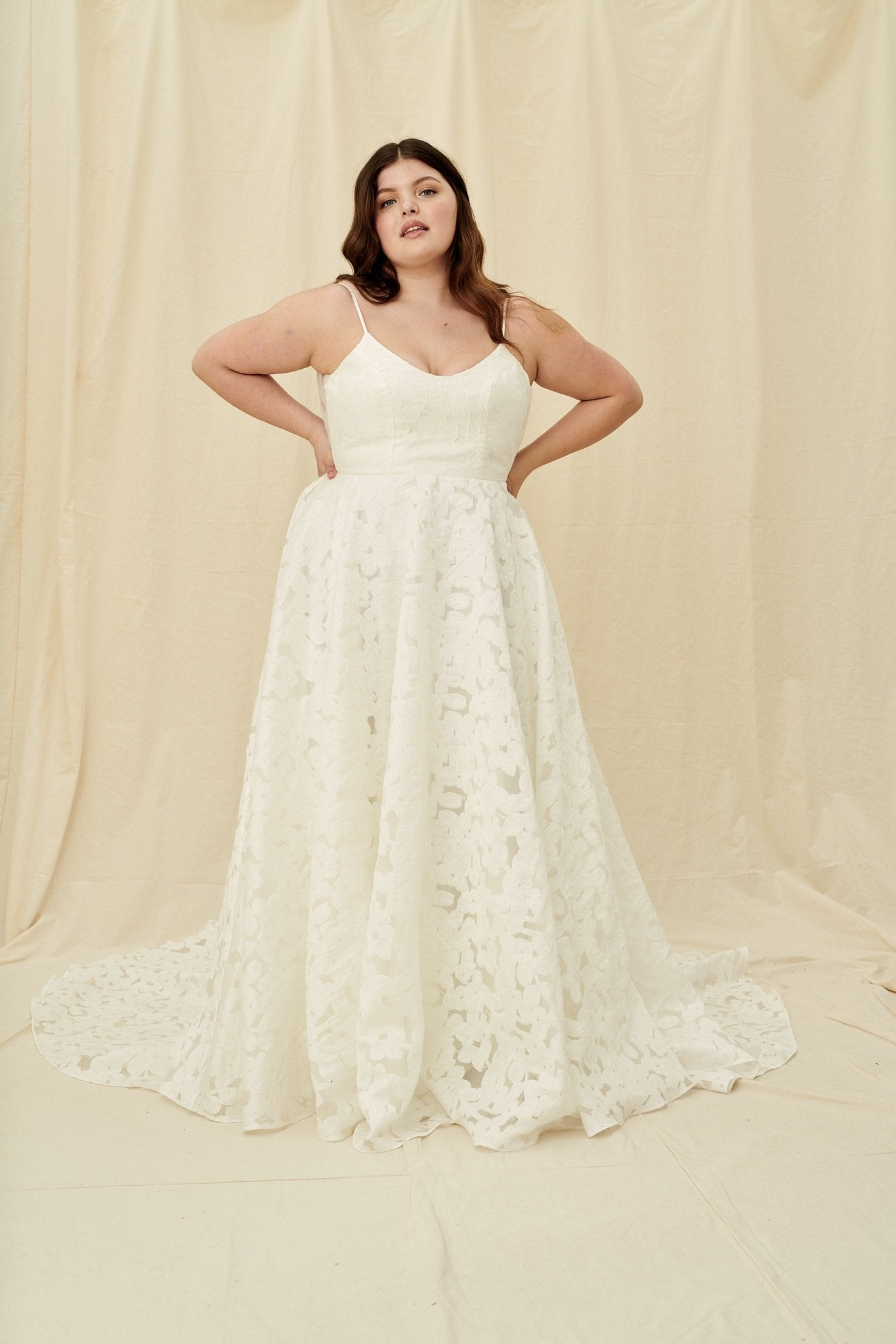 Plus size wedding dress in a floral lace print with a low scoop back, spaghetti straps, and a long train