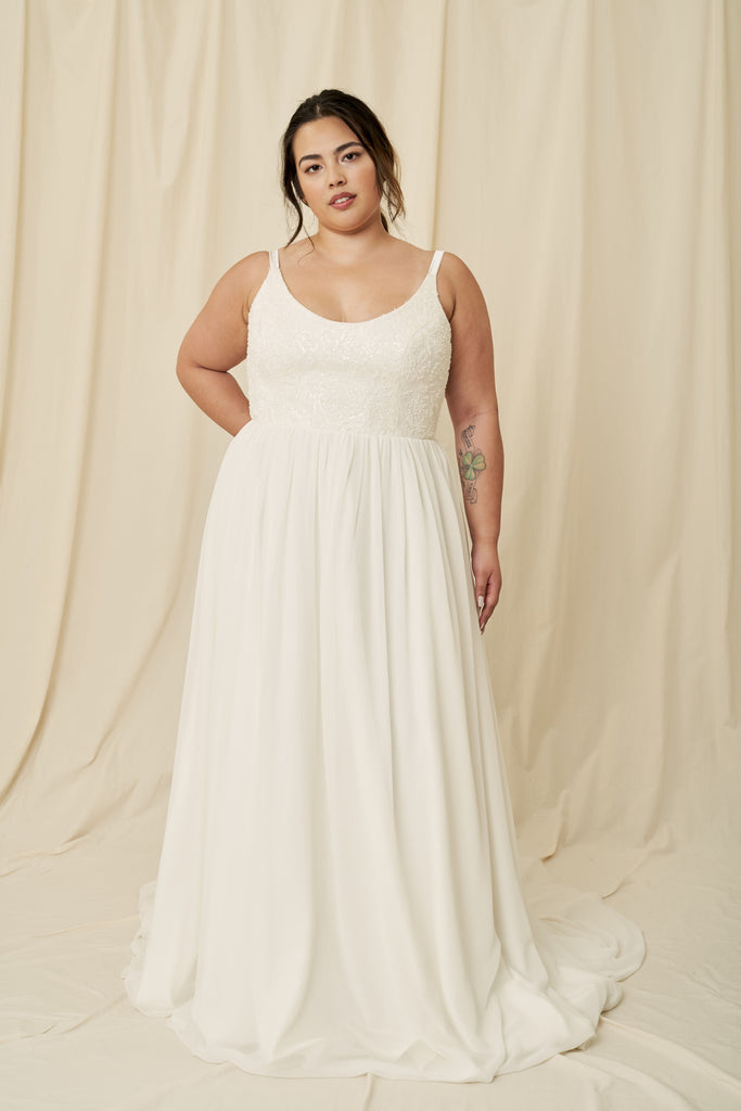 Plus size wedding dress with a low scoop back, delicate beading, and extra long chiffon train