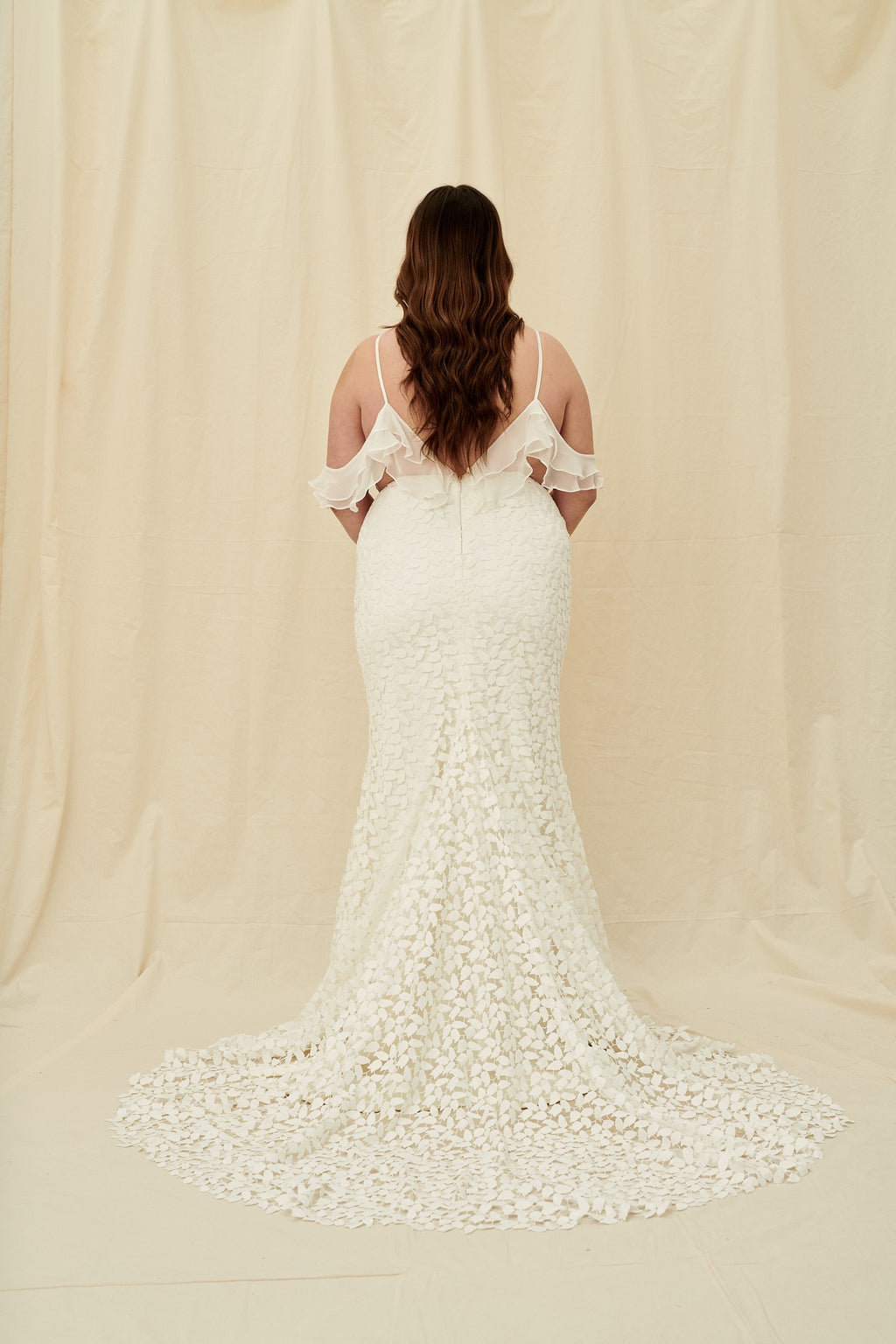 plus size fitted wedding gown with leafy lace, ruffles, and a long train