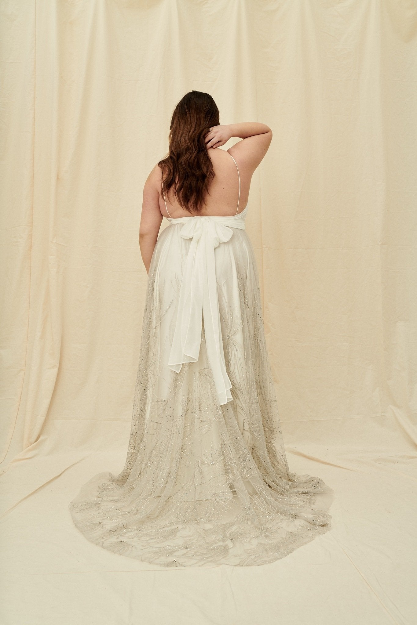 Plus size vintage-inspired wedding dress with silver beading, back ties, and a long train