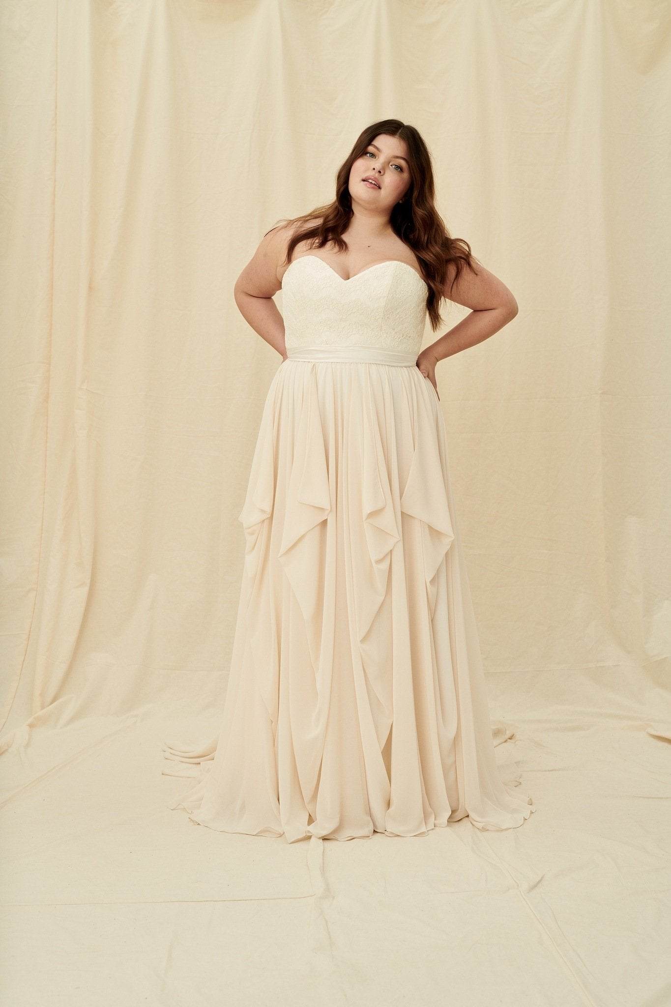 Plus size strapless sweetheart wedding dress with a corset back and a blush-coloured layered chiffon skirt