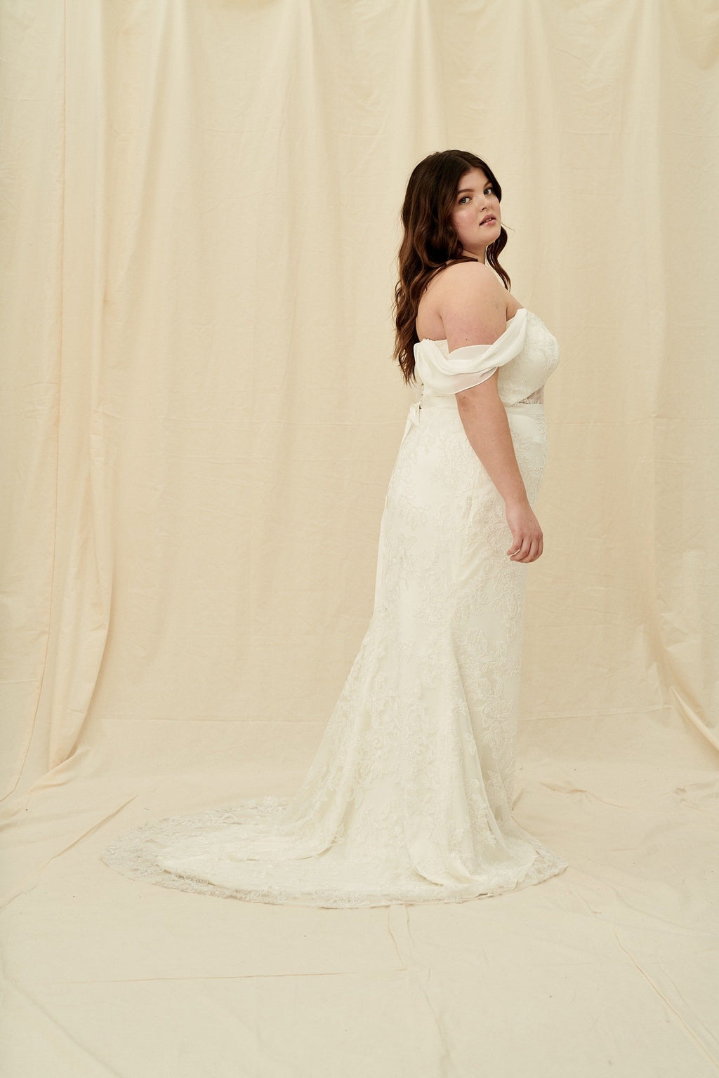Plus size mermaid wedding dress with a beaded sweetheart neckline, corset back, and draped cap sleeves