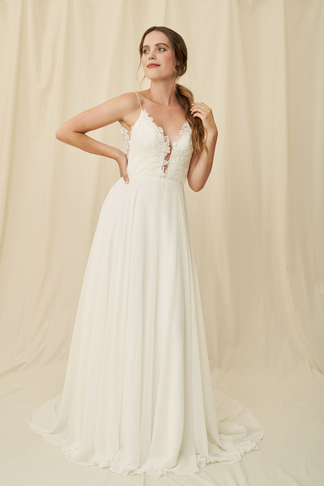 Flowy wedding dress with a low-cut lace bodice and sheer scoopback