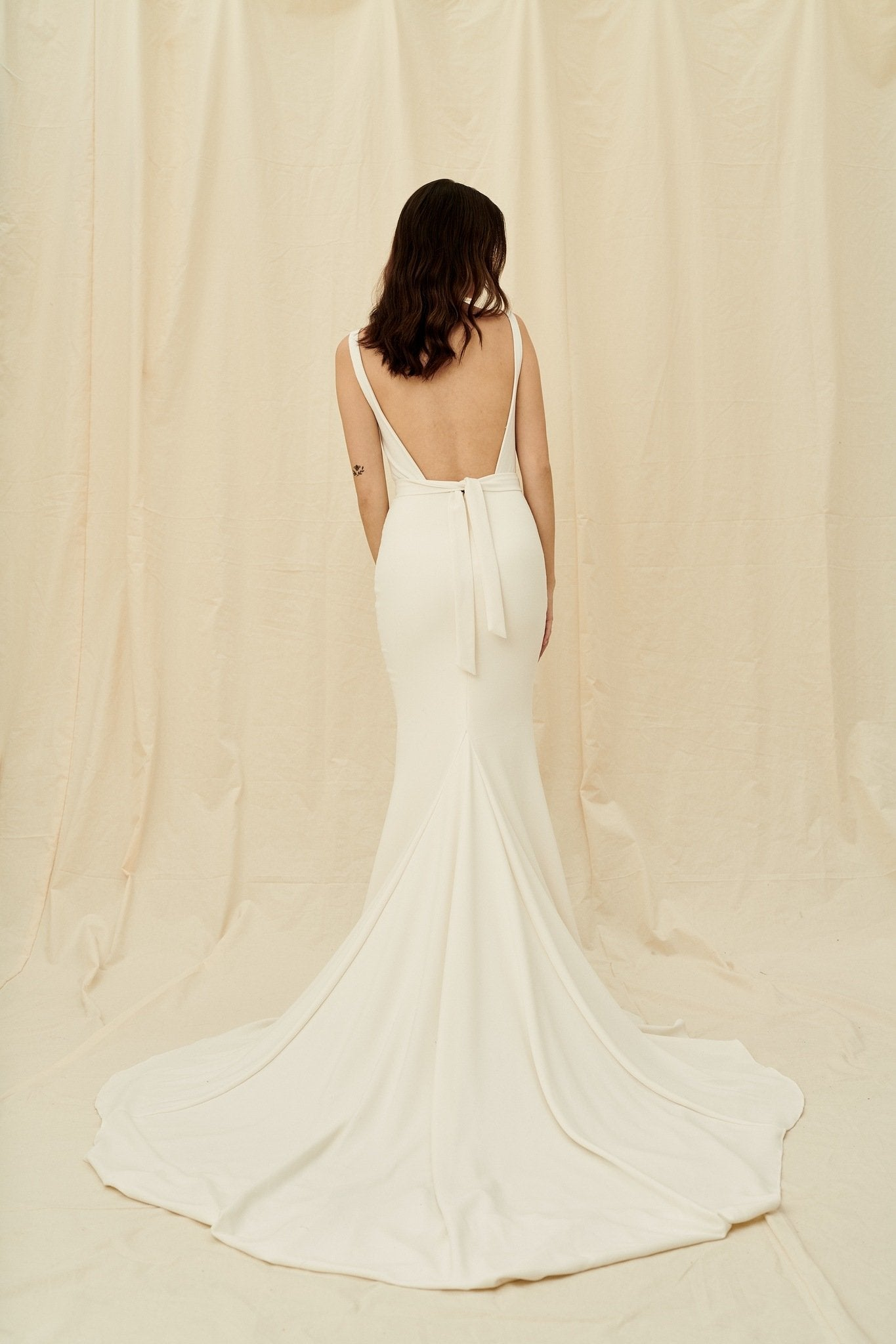 Backless crepe wedding dress with fitted skirt and a long train