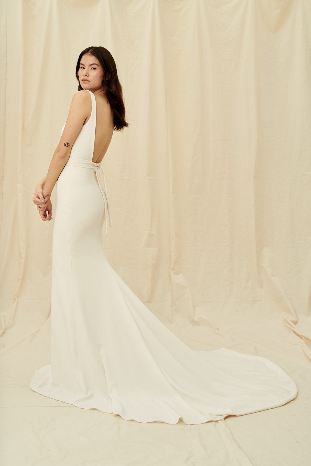 Minimalist crepe wedding dress with a square open back and a long train