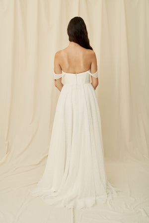 A straight across strapless wedding dress with a unique lace and off the shoulder sleeves by Truvelle