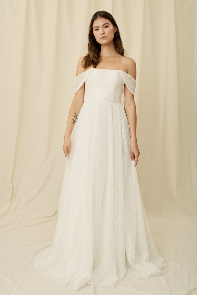 A straight across strapless wedding dress with a unique lace and off the shoulder sleeves