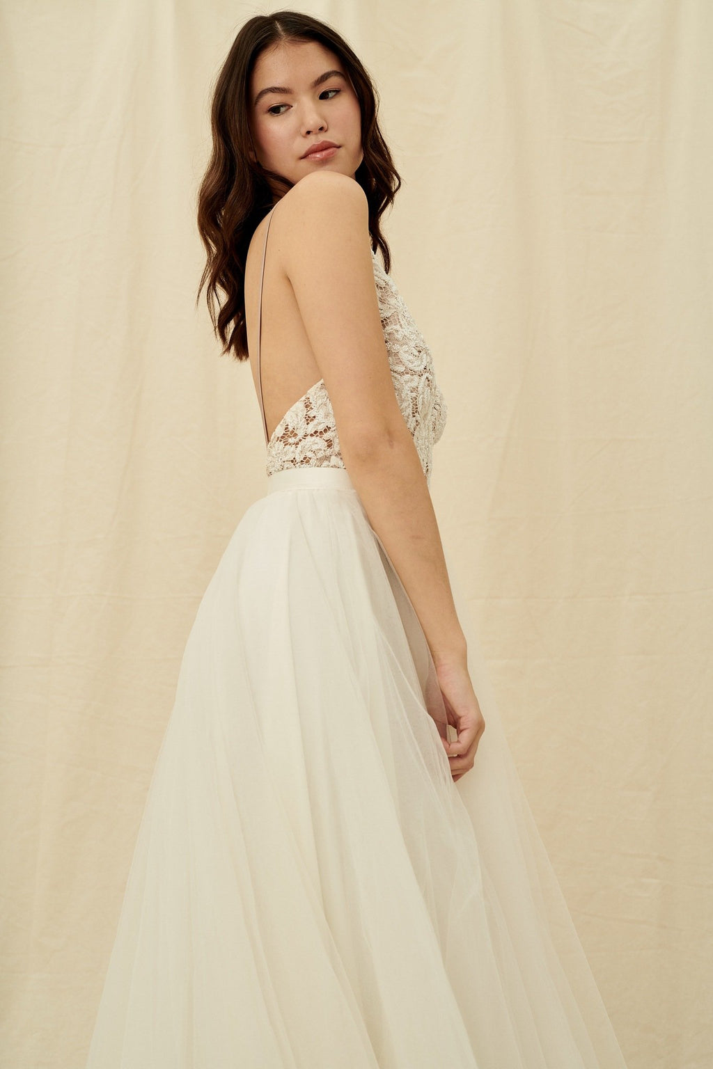 A princess wedding gown with a beaded bodice, open back, and tulle skirt with a train by Truvelle