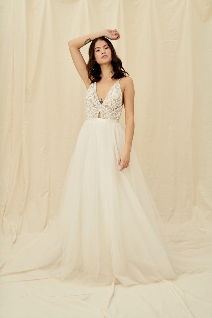 A princess wedding gown with a beaded bodice, open back, and tulle skirt with a train