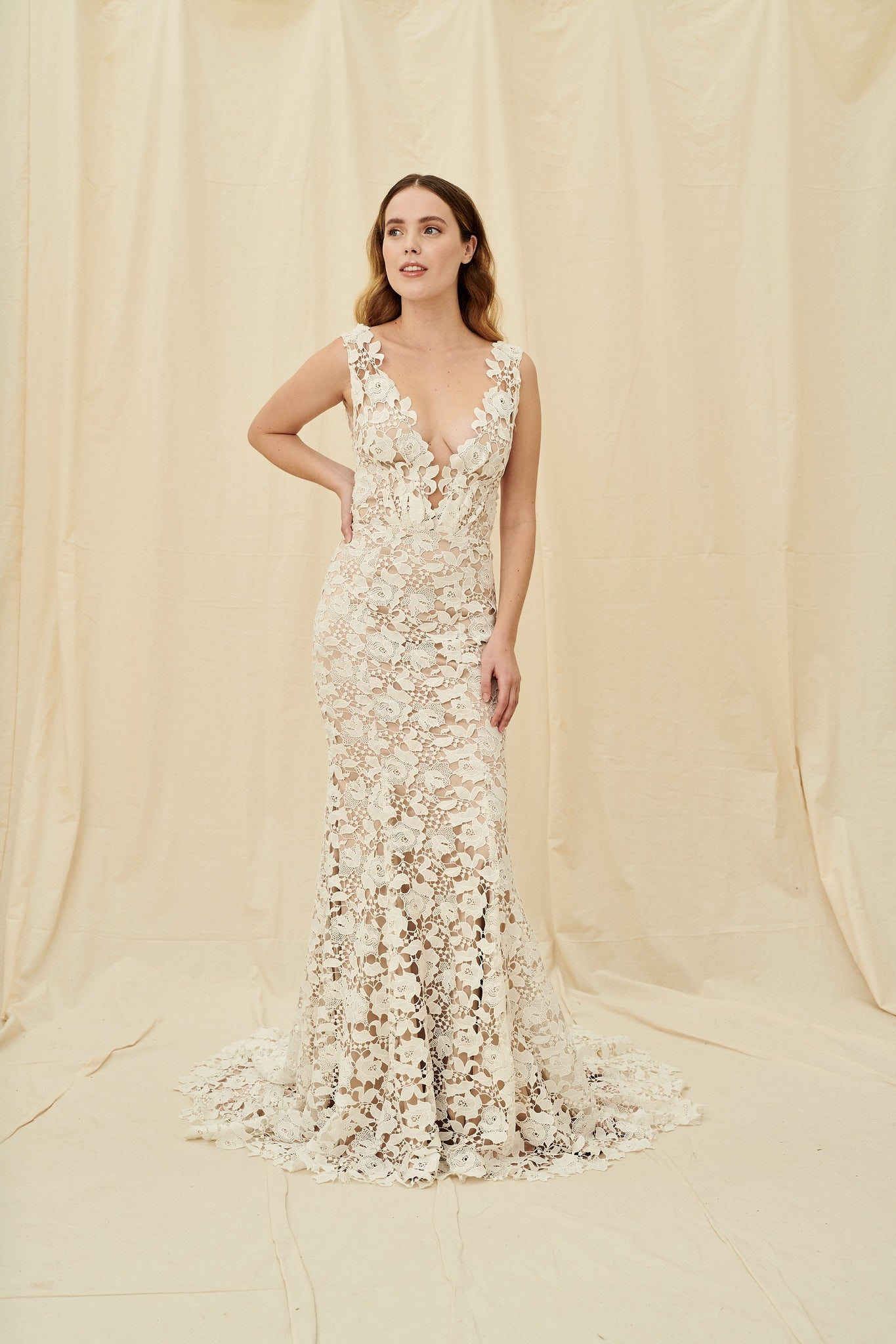 A fitted mermaid wedding gown with off-white floral lace over taupe lining