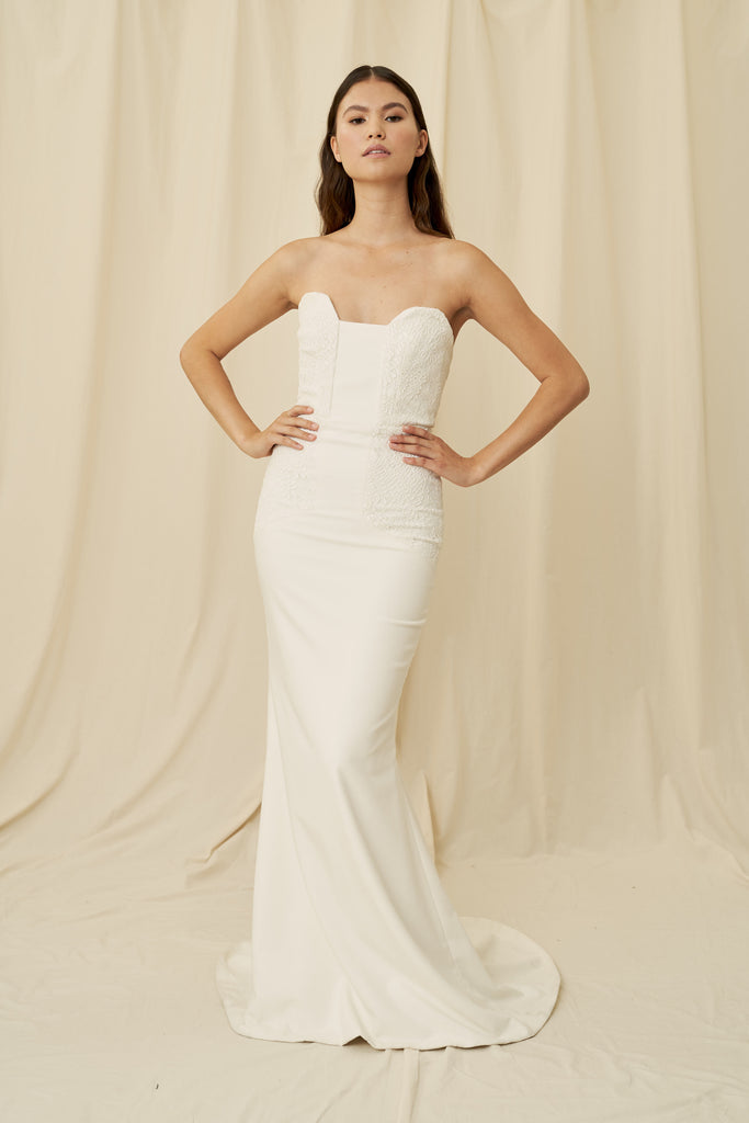 A unique angular strapless sweetheart wedding gown with lace panels and a train