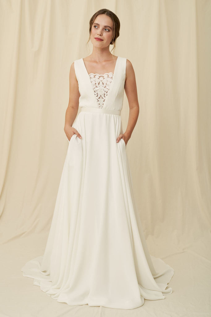 Elegant dress with a deep v back, beaded lace, and hidden pockets