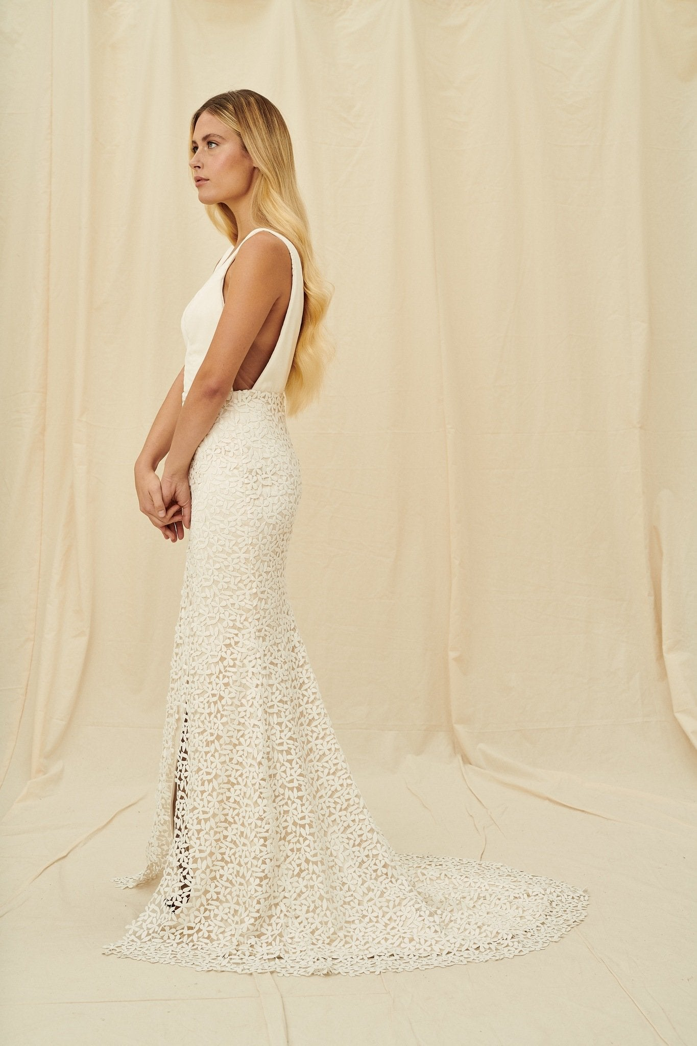 A mermaid wedding gown with a velvet v-neck bodice and floral lace slit skirt
