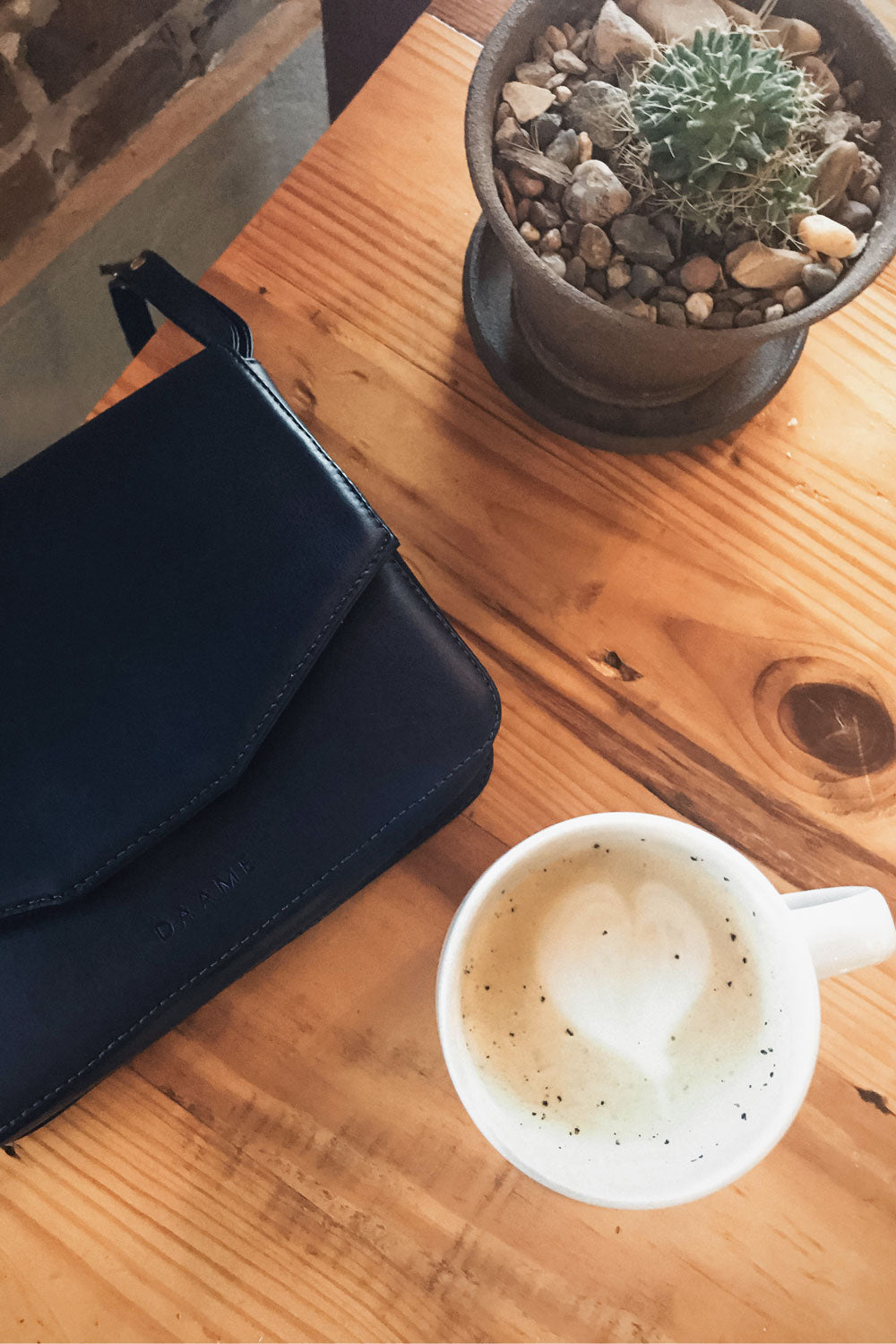 chic ethique drinking coffee with daame tate crossbody