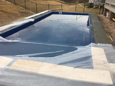 Installation of locking collar and travertine coping around fiberglass pool