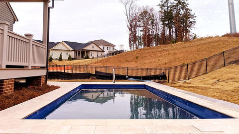 Hamptons style travertine decking around fiberglass swimming pool