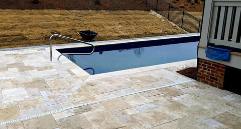 Deck drains installed in travertine decking with fiberglass pool