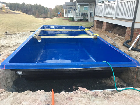 The fiberglass pool is stabilized with braces in the hole