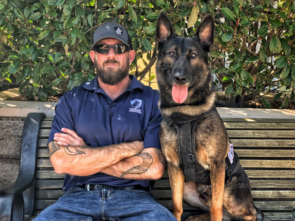 Mike Ritland seated with a black and brown protection dog on a bench.