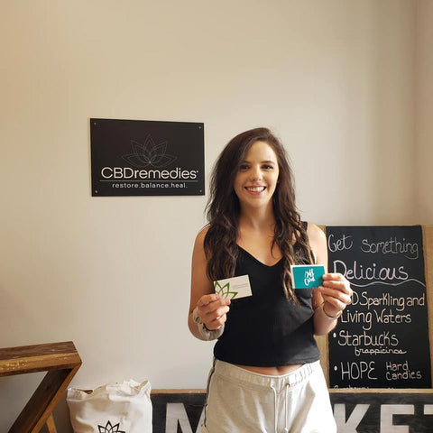 Kirsten, CBD Remedies Father's Day Surprise Gift winner holding CBD Remedies business cart and $50 gift card
