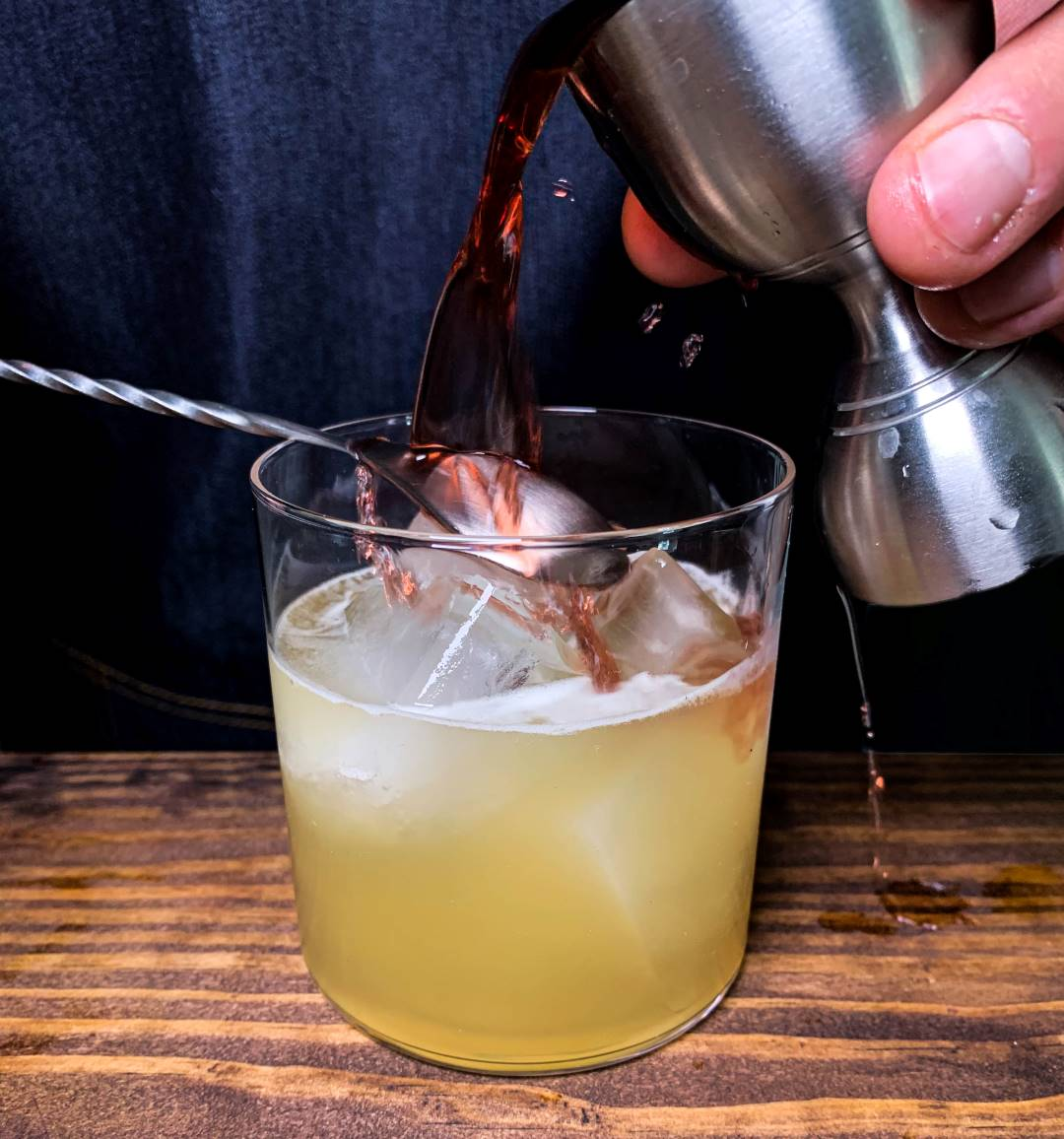 Red wine being poured on top of a whiskey sour making it into a New York Sour cocktail.