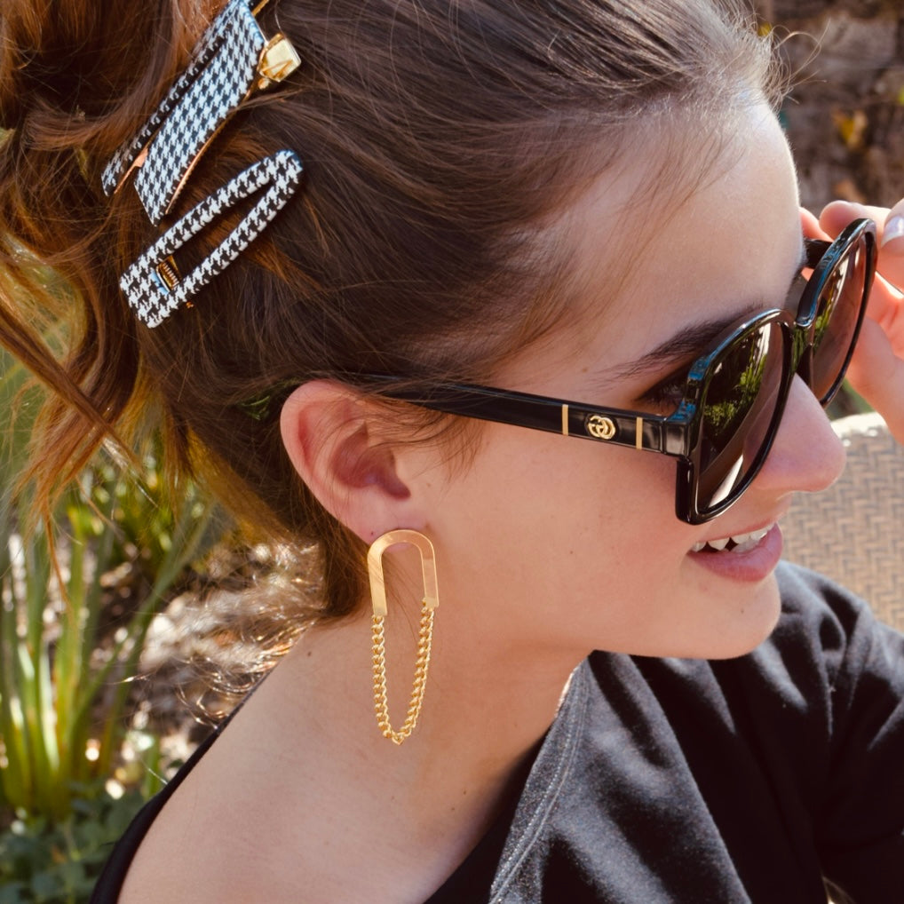 Model in sunglasses and gold paper clip earrings